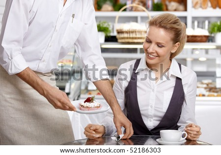 The waiter brings to the visitor the ordered dessert