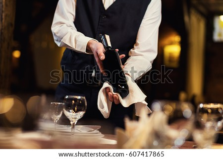 The waiter in uniform with a white towel offers visitors wine in restaurant