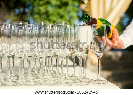 The waiter pours champagne into crystal glasses
