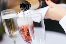 the waiter pours rose wine and champagne into the glasses
