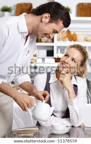 The waiter pours tea to the attractive girl
