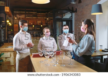 The waiters of the restaurant in a medical mask learns to distinguish between the glasses Foto d'archivio ©
