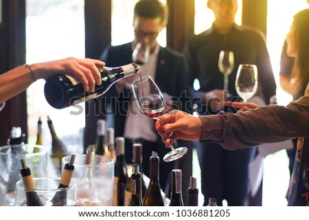 The waitress was pouring a glass of wine. In celebration of the team's success. - Shutterstock ID 1036881205