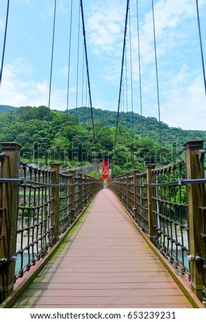 the walkway on red hanging bridge or suspension bridge above the green river in the valley, Wulai, Taiwan #653239231