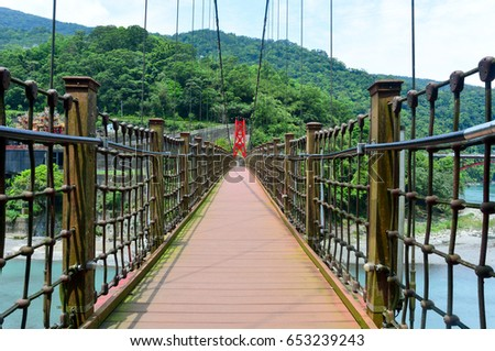 the walkway on red hanging bridge or suspension bridge above the green river in the valley, Wulai, Taiwan #653239243