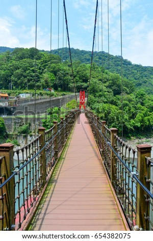 the walkway on red hanging bridge or suspension bridge above the green river in the valley, Wulai, Taiwan #654382075