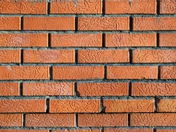 The wall is made of decorative red bricks. On the brick, neat grooves are visible, which fold into a pattern. Clean space. Abstract background with brickwork.