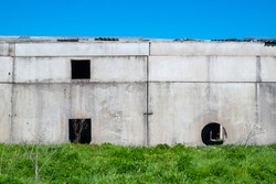 the wall of an old building made of concrete slabs. In the wall there are technological holes of square and round shape. the building is set against a background of green grass and blue sky