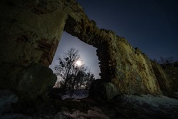 The wall of an old building with a hole in the winter. Entrance to an abandoned house. Ruins of an ancient castle at night.