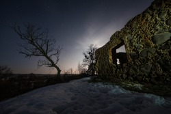 The wall of an old building with a hole in the winter. Window in an abandoned house on the edge of a hill. Ruins of an ancient castle at night. Silhouette of a dry dead tree.
