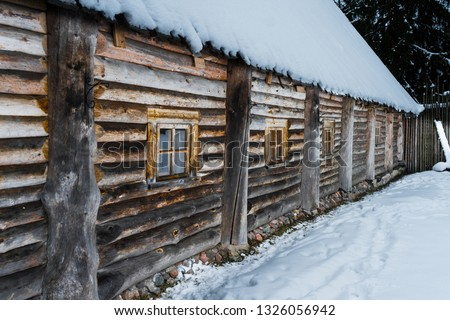 The wall of an old log house with small windows in winder landscape #1326056942