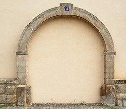 The walled up door with stone arch with metal rusty blue table with white number four on the ancient beige plastered walls background, photo frame, text place