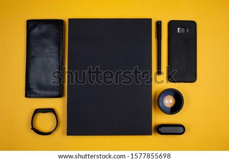 The wallet, sketchbook, pen, smartphone, fitness bracelet, lens and headphones case on Yellow background.