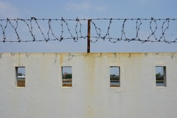 The walls of the building are made of concrete with sharp and sharp barbed iron wire at the top.