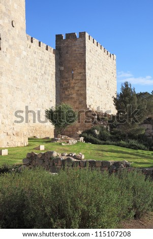 The walls of the eternal Jerusalem. The sunset gently illuminates the ancient walls and a green grassy lawn