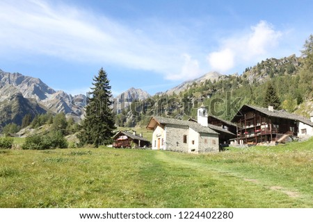 The Walser town of Follu, with wood and stone lodges, high mountains, forests and pastures, in summer, in Val d'Otro valley, Alps mountains, Italy Foto stock ©