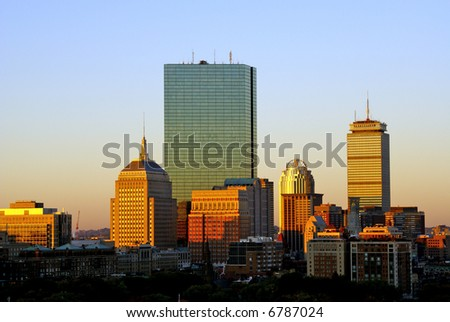 the warm color of the sun bathes the boston skyline on a cool autumn morning