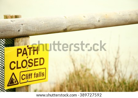 The warning path close cliff falls signage on the yellow color board background among the cliff scenery represent the caution and warning signage concept related idea.