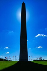 The Washington Monument casting a shadow on a sunny day.