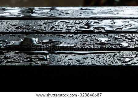 The water drops on wooden garden table, center focus for background.