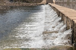 The water flow passes the weir from upper level to lower level the side stream of the river. The weir forms a small waterfall.