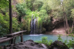 the water flows down the hill and flows into the lake, waterfall in a cozy natural place, board for jumping into the water near the waterfall