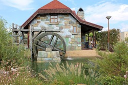 The water mill was built of colored stone under a tiled roof. A wooden wheel, from a gutter, water pours into the pond and rotates the wheel. Flowers and shrubs grow along the shore of the pond.
