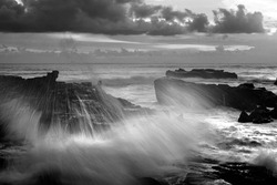 the water splash through the sea rock in mengening Rocky beach bali in black and white