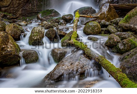 The waterfall flows over the stones. Mossy stones waterfall flow. Waterfall rocks view