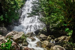 The waterfall flows through the rocks. The clear water is very strong flow. Waterfall from the top of the mountain is very high.