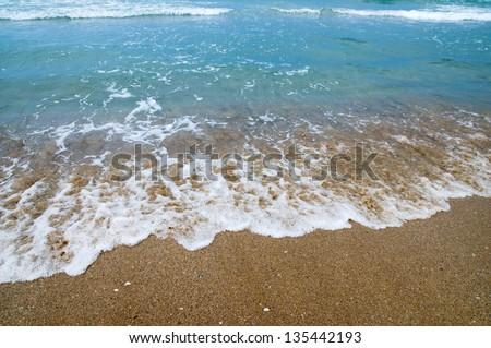 The wave surges on sandy coast