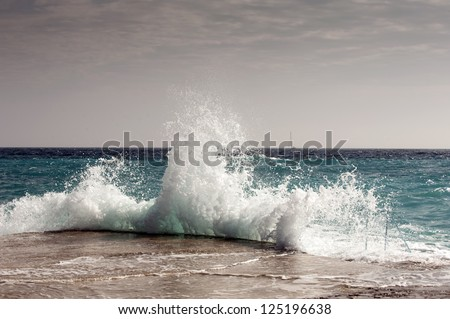 The waves breaking on a stony beach, forming a spray #125196638
