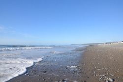 the waves calmly hitting the beach at borth foaming as it reaches the shore line