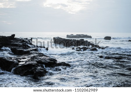 the waves of the ocean are breaking against the rocks. splashing ocean waves at sunset. #1102062989