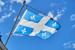 The waving flag of Quebec over a blue sky background. The flag of Quebec, called the Fleurdelise represents the Canadian province of Quebec, the flag consists of a white cross on a blue background