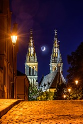 The Waxing crescent moon in between towers of basilica of St. Peter and Paul in Vysehrad, Prague.