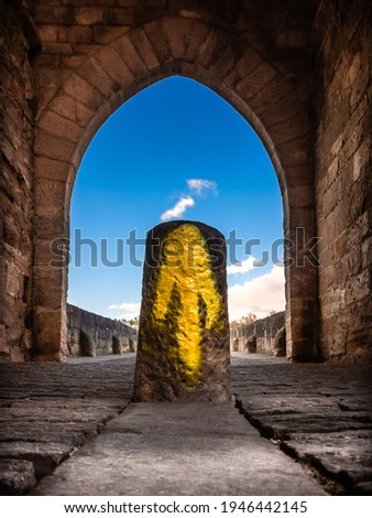 The Way Marking Post with Yellow Arrow Symbol Sign at the Arch Way by the Bridge in Puente la Reina, Navarra along the Trail of the Pilgrimage of St James Camino de Santiago Foto stock ©