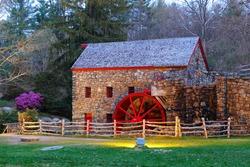 The Wayside Inn Grist Mill with water wheel after sunset, Sudbury Massachusetts USA