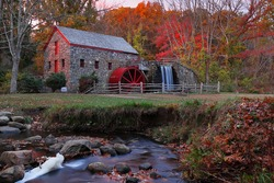 The Wayside Inn Grist Mill with water wheel and cascade water fall in Autumn at sunrise, Sudbury Massachusetts USA