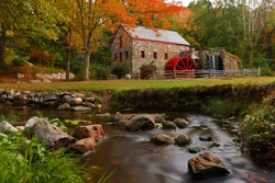 The Wayside Inn Grist Mill with water wheel and cascade water fall in Autumn, Sudbury Massachusetts USA