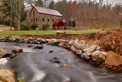 The Wayside Inn Grist Mill with water wheel and cascade water fall in spring, Sudbury Massachusetts USA