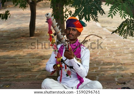 The wearing traditional wears playing musical instrument