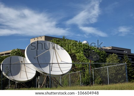 The Weather Forecast. The view of the white sattelite dishes and antenas on the blue sky and green background