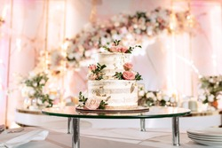The wedding cake. White, two-tiered, decorated with flowers and gold. On a delicate pink background. Side view, top.