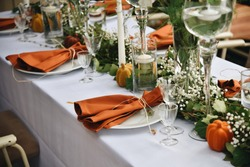 The Wedding Decor Rustic Style. Table Decoration Setting with Flowers Ivy and Pumpkins.
