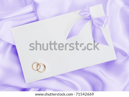 stock photo The wedding invitation with wedding rings on a violet