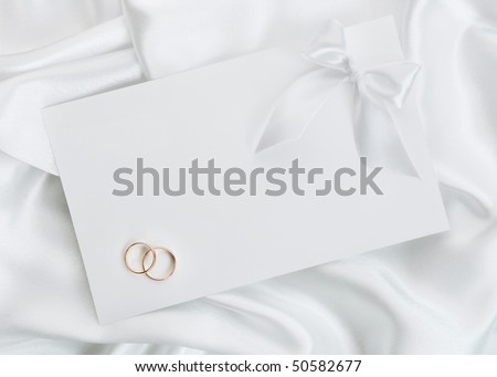 photo The wedding invitation with wedding rings on a white background