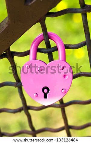 the wedding lock in the form of the heart, closed on the bridge. on the lock traces of negative impact of environment are visible