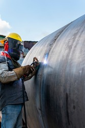 The welder is welding a large steel pipe with the process Flux Cored Arc Welding (FCAW) and dressed properly with personal protective equipment(PPE) for safety, at industrial factory.
