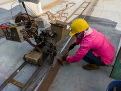 The welder is welding add joint a steel plate with process Submerged Arc Welding(SAW) at industrial factory.